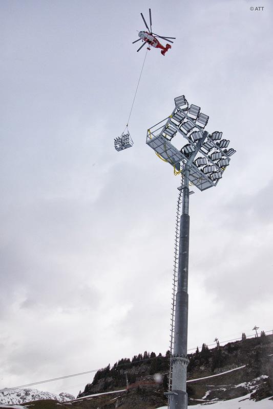 Montage par hélicoptère mat éclairage sur stade d'hiver en montagne