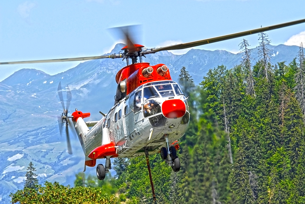SUPER PUMA lift in forest - Contact us - Helilift operation in Europe - Helicopter services transport external load
