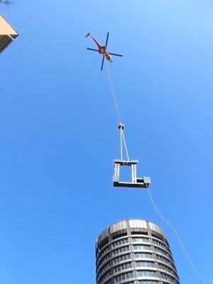 Hélicoptère en grutage d'une pièce de climatiseur, levage sur un imeuble en ville - Opération de levage urbain avec autorisation France